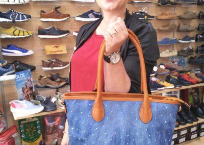 Bolso color azul expuesto por una modelo posando.