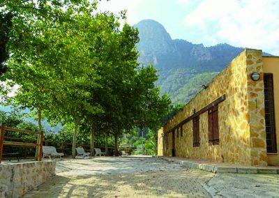 Imagen de la puerta principal y terraza delantera junto a su entorno del Albergue la Atalaya de Cieza.